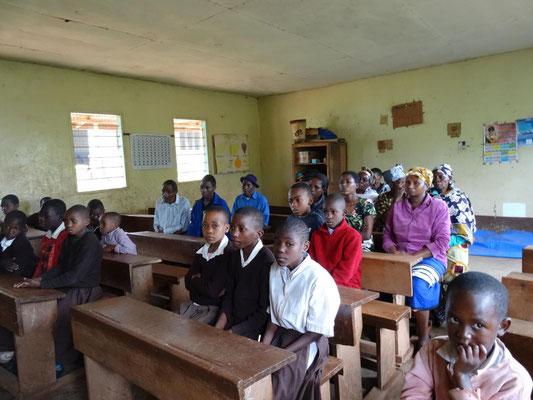 Versammlung von 20 unterstützten Schülern unserer Grundschul-Spendenaktion und ihrer Erziehungsberechtigten in der Materuni-Grundschule.