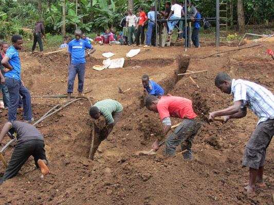 Schüler beim Einebnen des Umfeldes vom Jungenhaus durch Abtragen von Erde.