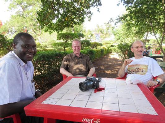 Bei der Hitze tut eine Pause im Schatten gut: Br. Shija, Leiter unserer Partner-Berufsschule (VTC) in Moshi, mit Michael Link und mir im Uhuru-Park in Moshi.