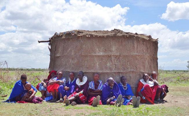 Massaifrauen suchen im Schatten einer Hütte Schutz vor der Mittagshitze .