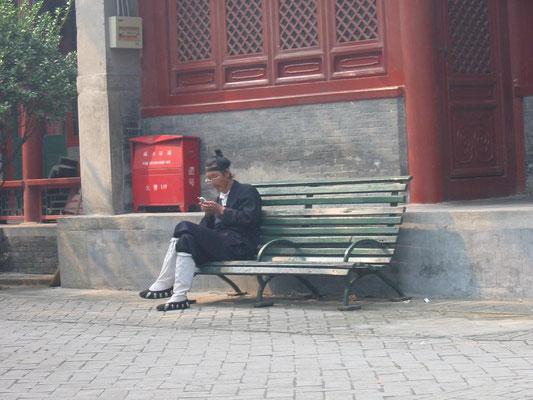 Moderne trifft Tradition: ein Mönch tippt eine SMS ins Handy (Peking 2005).