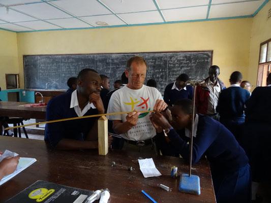 Hr. Pieke unterstützt Schüler kurz im Physikunterricht bei einem Experiment zu den Hebelgesetzen.