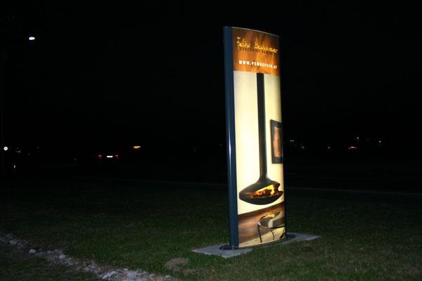 bombierter Werbeturm, hinterleuchtet mit Leuchtstoffröhren