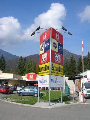 Werbeturm mit beschrifteten Schildern, angestrahlt mit Flutern
