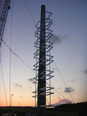 Werbeturm mit Schleuderbetonmast und Stahlkonstruktion bei der Montage