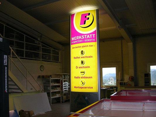 bombierter Werbeturm,beschriftet im transluzenten Folien,  hinterleuchtet mit Leuchtstoffröhren