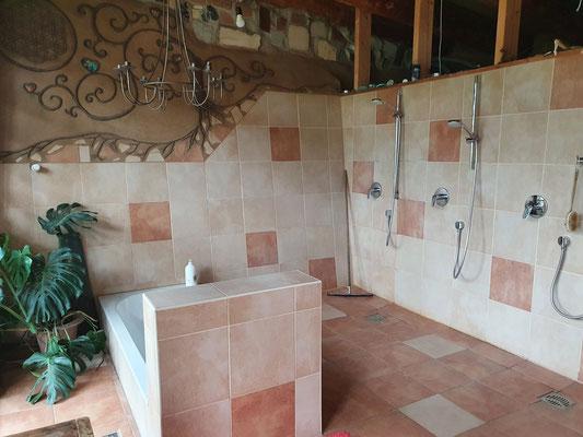 Badezimmer mit Badewanne und Duschen