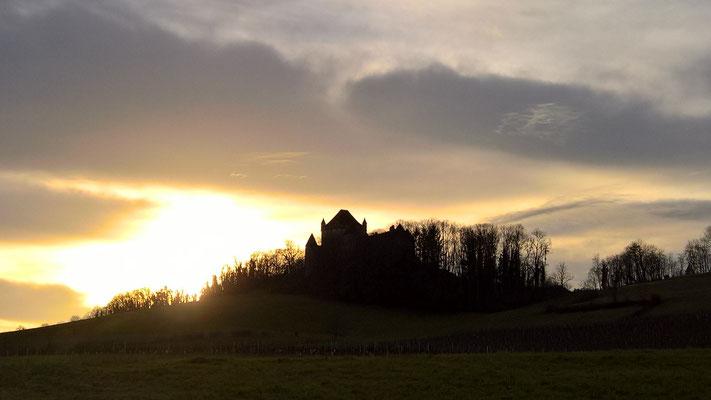 Die Sonne verschwindet zwischen dichten Wolken, hinter einer kleinen Burg