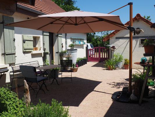 Der neue Sonnenschirm bringt herrlichen Schatten auf die sehr helle Terrasse