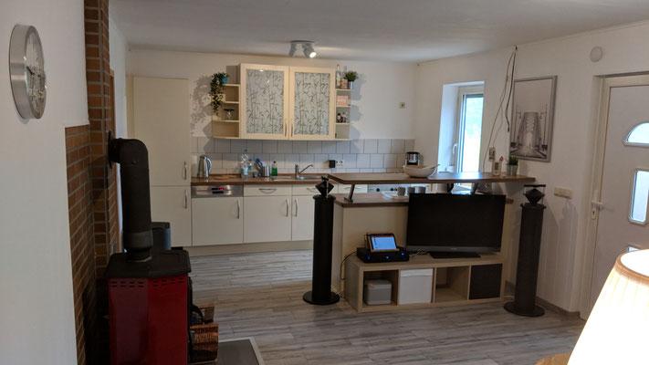 Blick im Wohnbereich auf die Küche und Medienboard