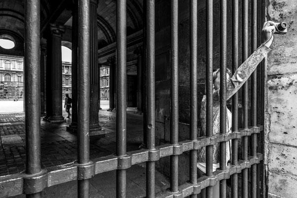 Une femme, bloquée par les grilles, photographie les alentours