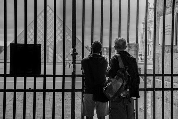 Deux touristes admirent la pyramide derrière des grilles