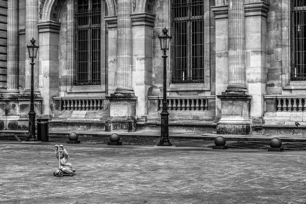 Un enfant joue seul dans la cour pavée du Louvre
