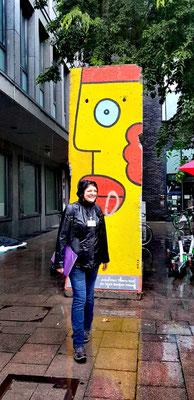 Le sourire même sous la pluie devant un morceau du mur de Berlin