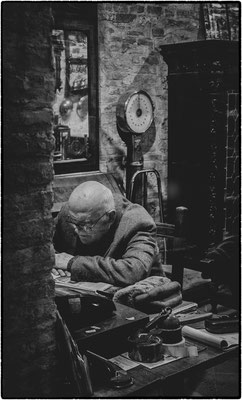 shop owner reading the newspaper, san gimigiano, italy