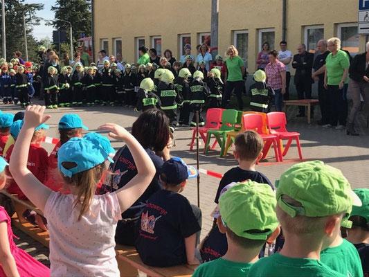 Szene eines Kinderfestes an einer Schule, auf dem sich die Feuerwehr mit ihrer Jugendarbeit präsentiert.