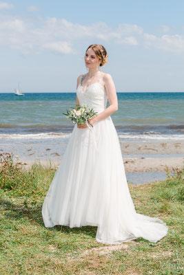 Braut am Strand vor dem Leuchtturm Falshöft