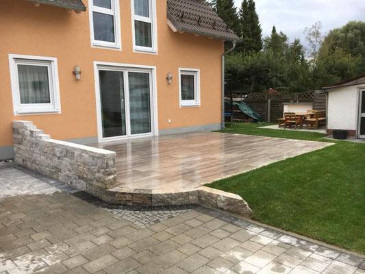 Terrasse mit Feinsteinzeugplatten belegt, Einfassung mit Einzeiler und Natursteinmauer aus Kalksandstein