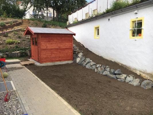 Hang abgetragen, Stützmauer mit Wasserbausteinen erstellt und Platz für ein Gartenhaus geschaffen.