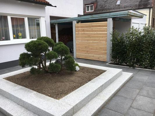 Moderner Vorgarten mit Lärchensichtschutzelementen an Granitsäulen.