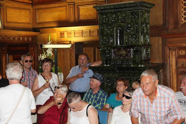 Bürgermeister Erich Hegwein lehnt weinselig am Kachelofen