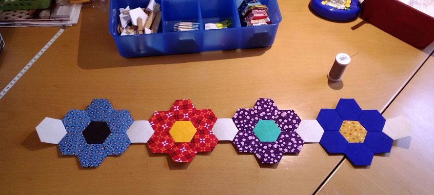Dann werden die Blumen mit Zwischen-Hexagons in Reihen zusammen genäht. Danach werden die einzelnen Reihen zusammengenäht.