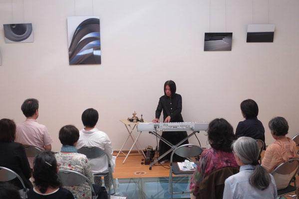 井坂先生の作品を背にして演奏する金大偉 氏