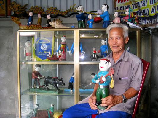 Ein alter Mann präsentiert stolz seine Puppen für das berühmte Wasserpuppentheater von Hanoi