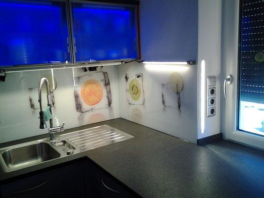 Glasrückwand mit eigenen Fotos gestaltet, Oberschränke mit Glasrahmen und farbigen LED´s schließen die Küche ab