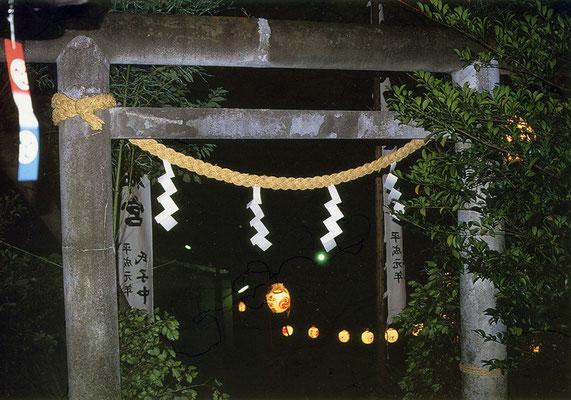 森山神社本殿横の石の鳥居からお囃子舞台をのぞむ