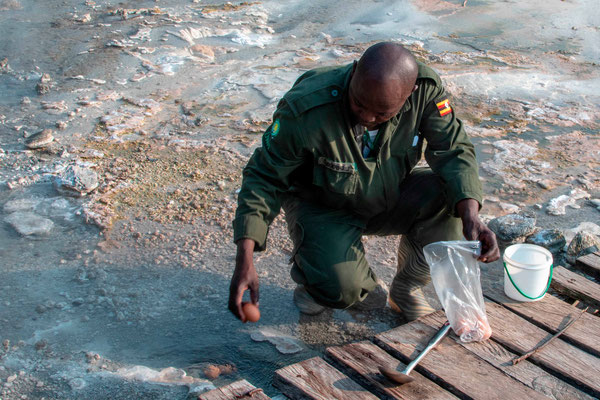 Justice, a Semiliki ranger with a passion for entomology, cooks us an egg in the Semuliki hot springs.