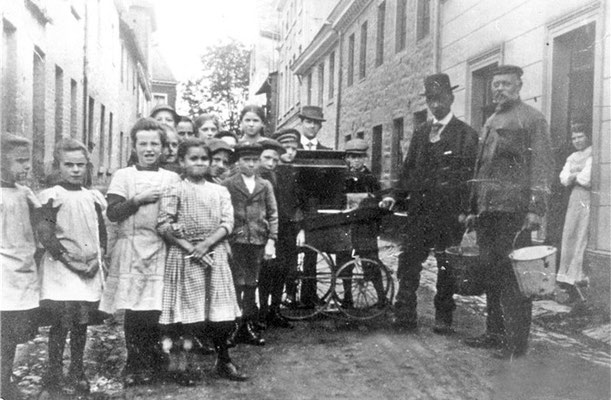 Jupp Dohm besaß eine Spielorgel. Zur Kirmes wurde er engagiert. Dann lieferte er Karussellmusik. Von morgens bis abends drehte er unermüdlich seine Orgel. Auf dem Foto spielt er mit seiner Orgel in der Heggenstraße.