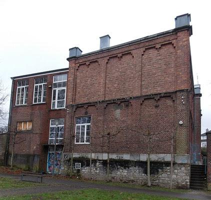 Die Außenwände der Seitentrakte sind fast fensterlos, doch durch Mauerwerksblenden und Friese aus Backstein strukturiert und verziert.