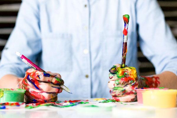 künstler sitzt mit verschmierten pinseln und ölfarben vor einem tisch