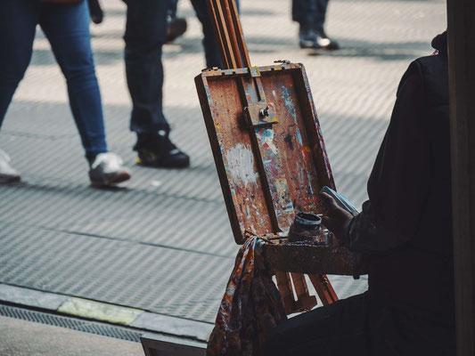 künstler in einer stadt malt auf einer staffellei