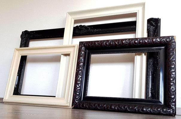 vier bilderrahmen an einer wand gestellt-weiße und schwarze rahmen