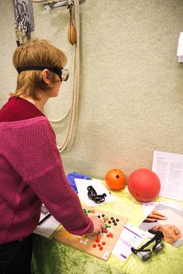 Eine Lehrkraft experimentiert mit einer Brille, die ein stark eingeschränktes Sichtfeld simuliert