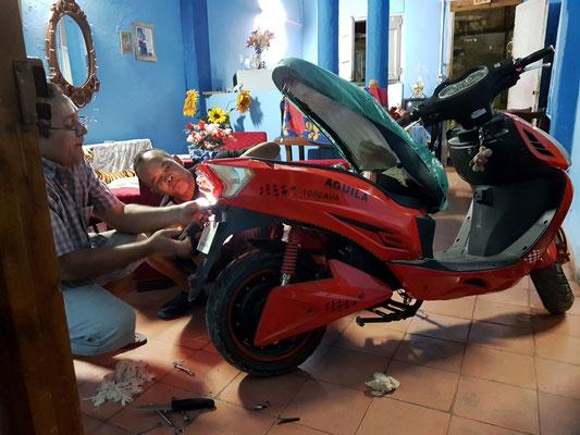 Abendliche Reparatur eines Motorrollers im kubanischen Wohnzimmer