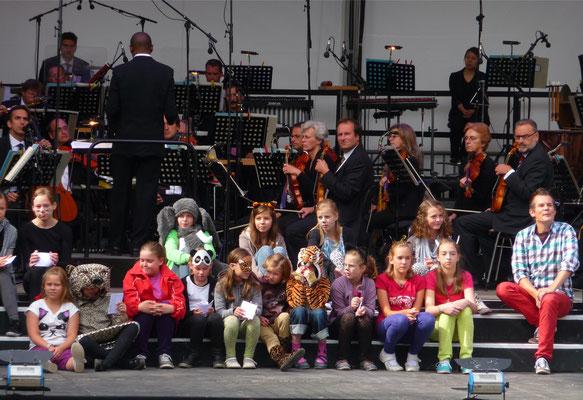 Classix For Kids, Gastgeber ist Malte Arkona. Am Dirigentenpult des Sinfonieorchesters Aachen steht GMD Kazem Abdullah.
