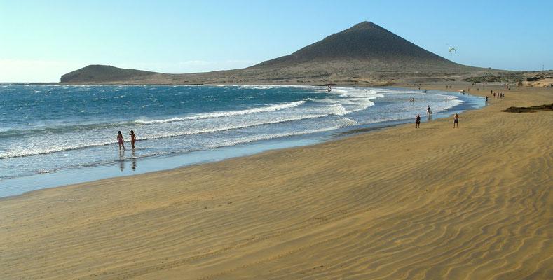 El Medano mit seinem schönen Sandstrand, ein Eldorado für Surfer, im Hintergrund die Montaña Roja