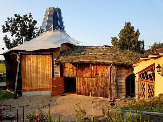 Das Theatergebäude, eine Holzkonstruktion mit Stahleinlagen, Gründach, Solarkuppel und Bullerjahn (Kaminofen)