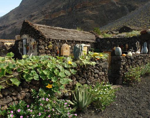 Lavasteinhäuser des Museumsdorfes Guinea vor der Steilwand Fuga de la Gorreta