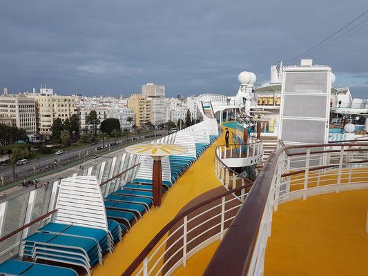 Blick vom Oberdeck auf das Sonnendeck der AIDAmar (Voschiff) und zur Avenida del Puerto von Cádiz