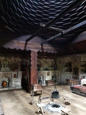 Innenraum eines ostgeorgischen Bauernhauses mit Ältestenstuhl und offener Kuppelkonstruktion über der Feuerstelle (Kartli)