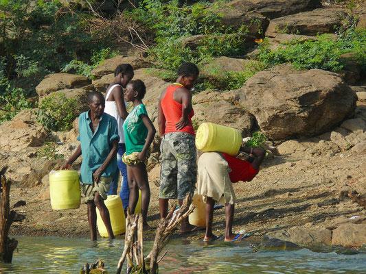 Wasser wird vom See zu den Hütten geschleppt.