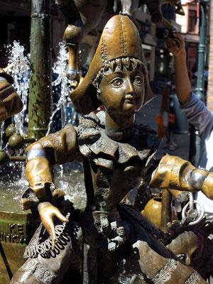 Puppenbrunnen. Professor (hier nicht sichtbar) und Harlekin stehen für Lehre und Kultur.