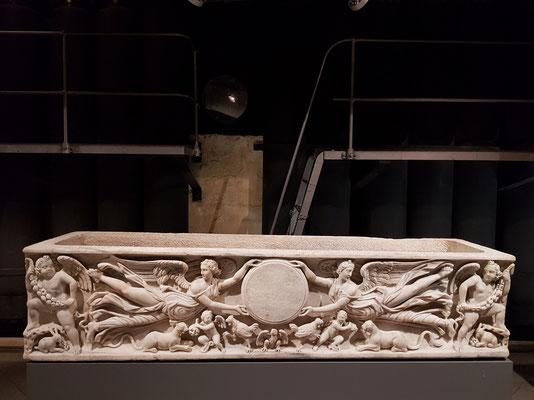 Sarkophag mit zwei eleganten geflügelten Siegesgöttinnen, die einen runden Rahmen (Clipeo) halten, dazu Bezüge zu einer dionysischen Welt, letztes Viertel des 2. Jh. n.Chr.