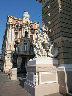 Operhaus. Auf der Eingangsebene befinden sich rechts und links des Haupteingangs zwei Figurengruppen, die die Komödie und die Tragödie darstellen.