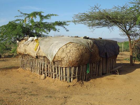 Typische Hütte der Samburo  aus einem Stangengeflecht, das mit Kuhdung, Lehm, Tierhäuten oder Grasmatten bedeckt ist. In diesem Falle zeigt die Plastikplane den Einzug der neuen Zeit.