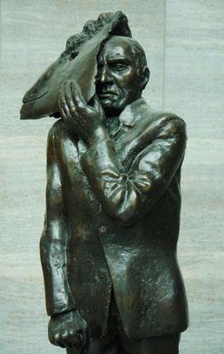 """Wolfgang Mattheuer: """"Gesichtzeigen"""", Bronze. 1981 – Mann mit Maske (Maskenmann). In Erinnerung an die Montagsdemonstrationen wurde die in mehreren Güssen verbreitete Plastik in Leipzig in """"Gesichtzeigen"""" umbenannt."""